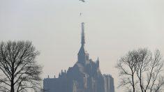 Imagen del momento en el que un helicóptero retira la estatua del arcángel San Miguel en la abadía que lleva su nombre, en Normandía. (AFP)