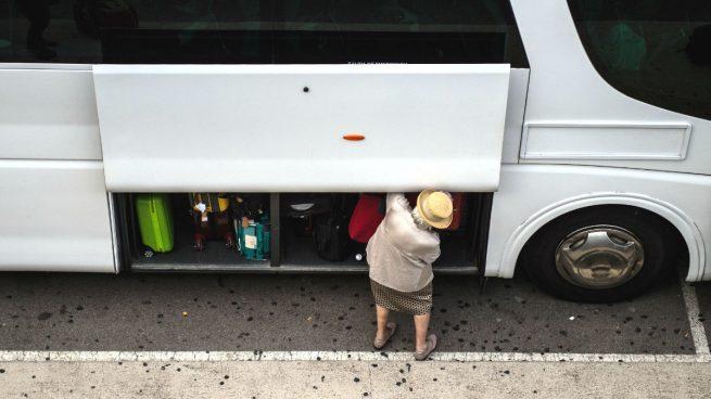 Una pasajera guarda su equipaje en un autobús.