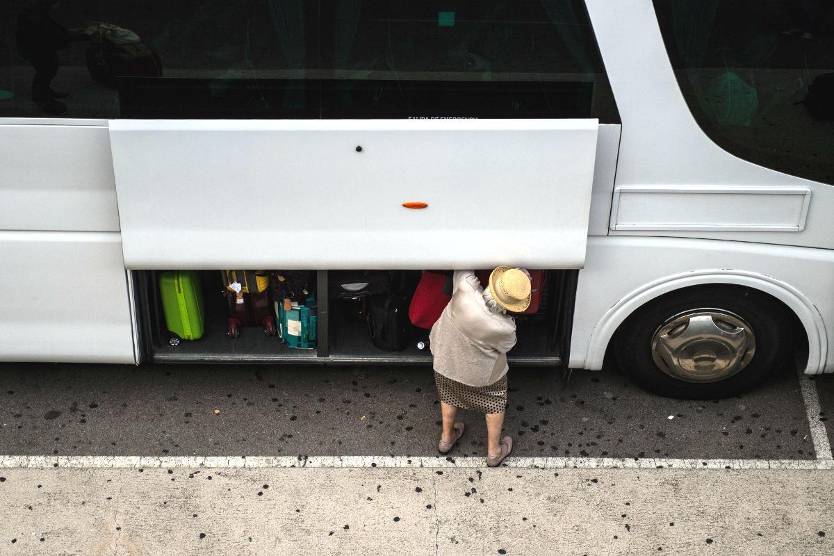 Una pasajera guarda su equipaje en un autobús (Foto: GETTY).