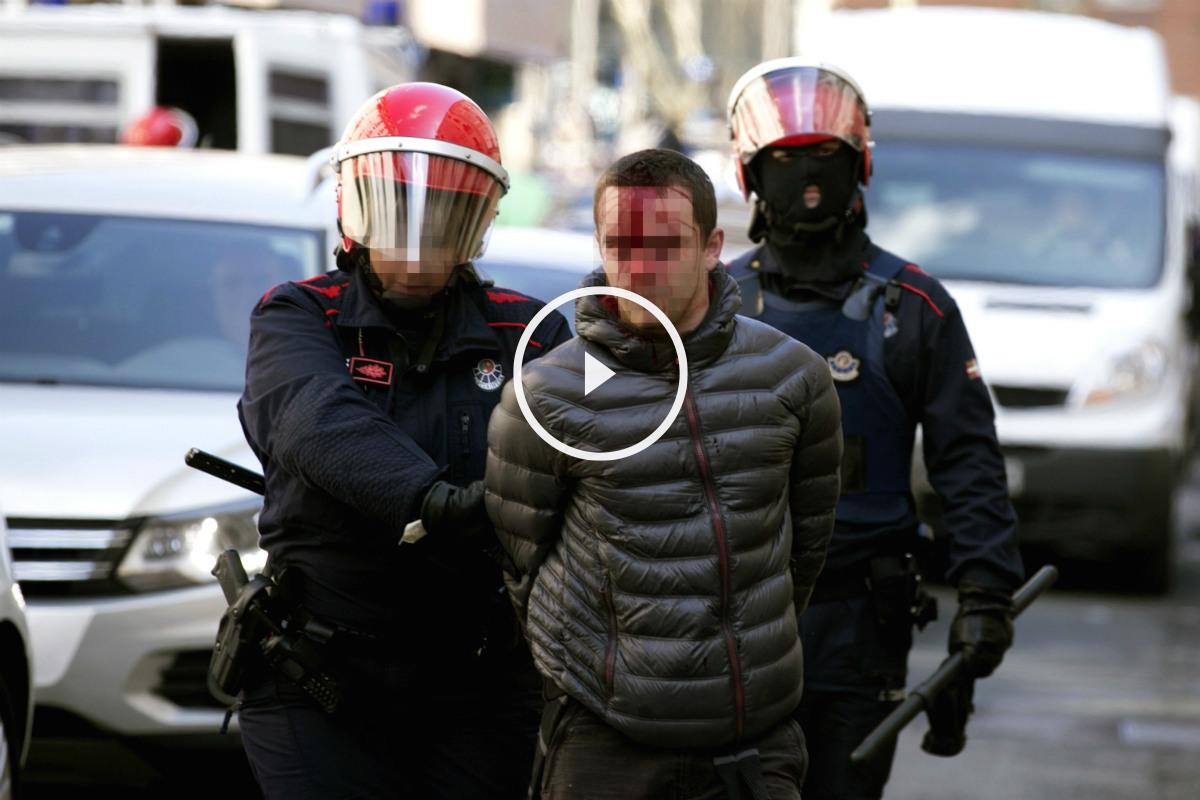 Dos antidisturbios de la Ertzaintza custodian a uno de los detenidos en Vitoria. (EFE)