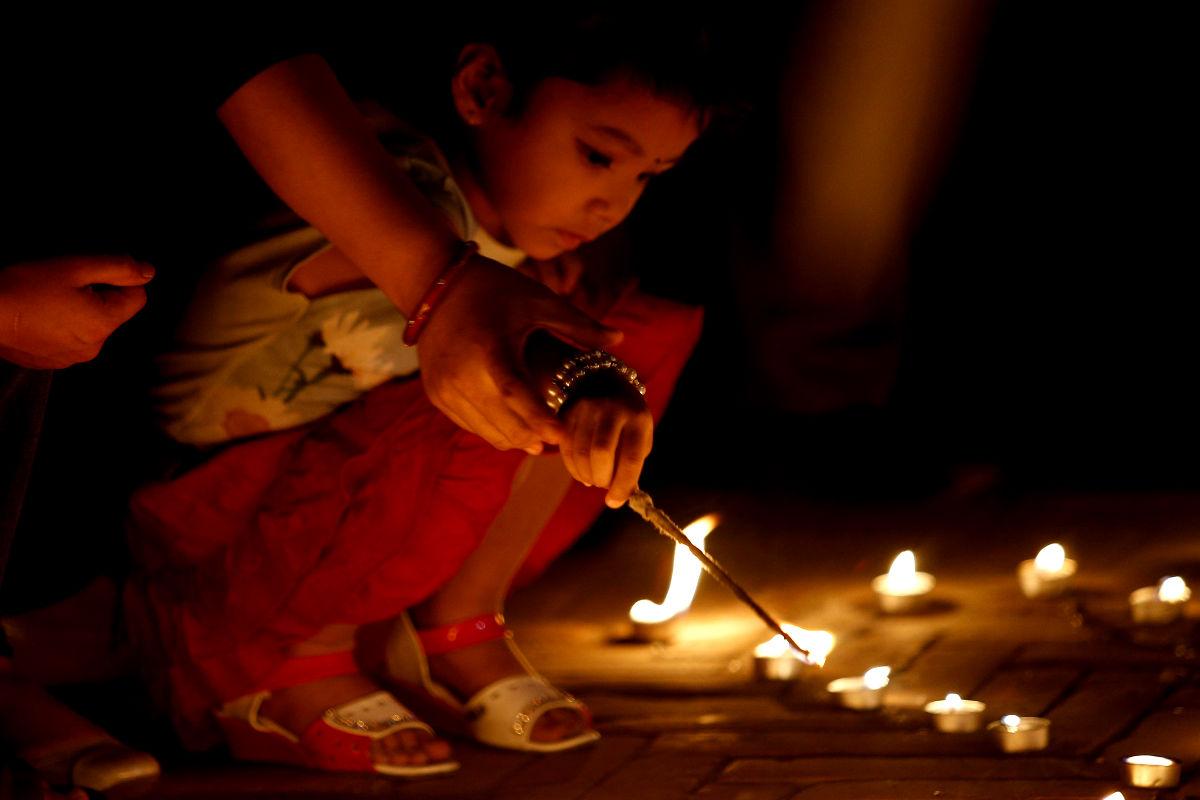 Imagen de una niña nepalí encendiendo una vela por las víctimas. (Getty)