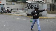 Un hombre prepara una piedra para lanzar durante la pelea entre opositores y chavistas en la Asamblea Nacional de Caracas. (Reuters)