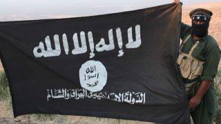 Un yihadista sujeta la bandera del Estado Islámico.