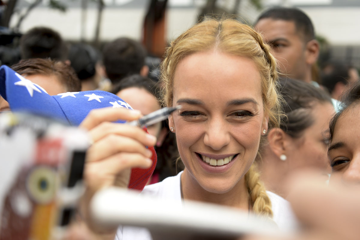 Lilian Tintori, boli en mano para firmar contra Maduro. (Foto: AFP)
