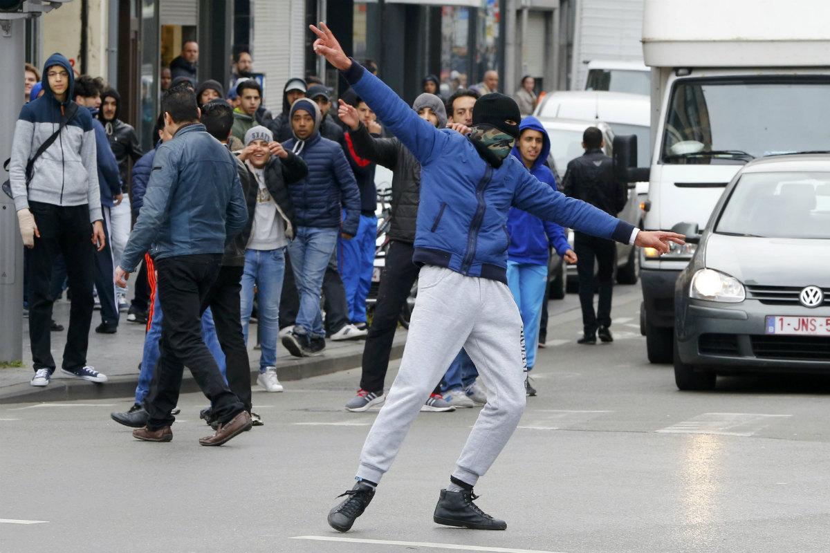 Varios jóvenes se manifiestan con la cara tapada en el distrito bruselense de Molenbeek. (Reuters)