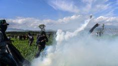 Un grupo de refugiados en Idomeni se defiende de la policía que lanza botes de gas lacrimógeno. (Foto: AFP)