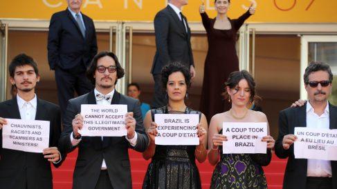 El equipo de Aquarius aprovecharon la atención mediática de la alfombra roja de Cannes para mostrar pancartas contrarias a la destitución de Dilma Roussef. Detrás, la actriz Sonia Braga apoya a sus compatriotas. (Foto: AFP)