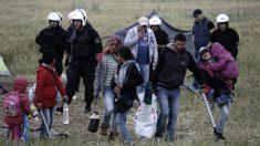 Agentes de la policía griega desalojan a una familia del campo irregular de refugiados de Idomeni. (AFP)