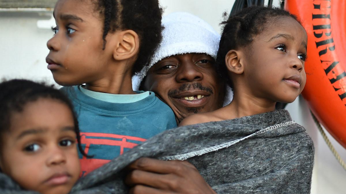 Un padre abraza a sus hijas a bordo del barco de rescate 'Aquarius' (AFP)