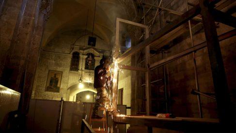 Un operario en la tumba de Cristo en la iglesia del Santo Sepulcro en Jerusalén. (Foto: AFP)