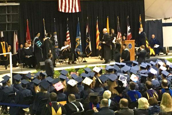 Panorámica del acto de graduación en la Universidad de Graceland (Iowa, EEUU) con la estelada sobre el estrado.