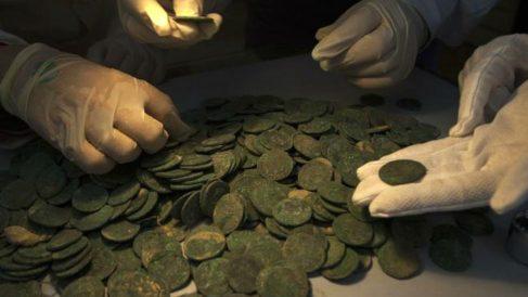 Técnicos del Museo Arqueológico de Sevilla analizan las monedas descubiertas en este magnífico hallazgo. (Foto: AFP)