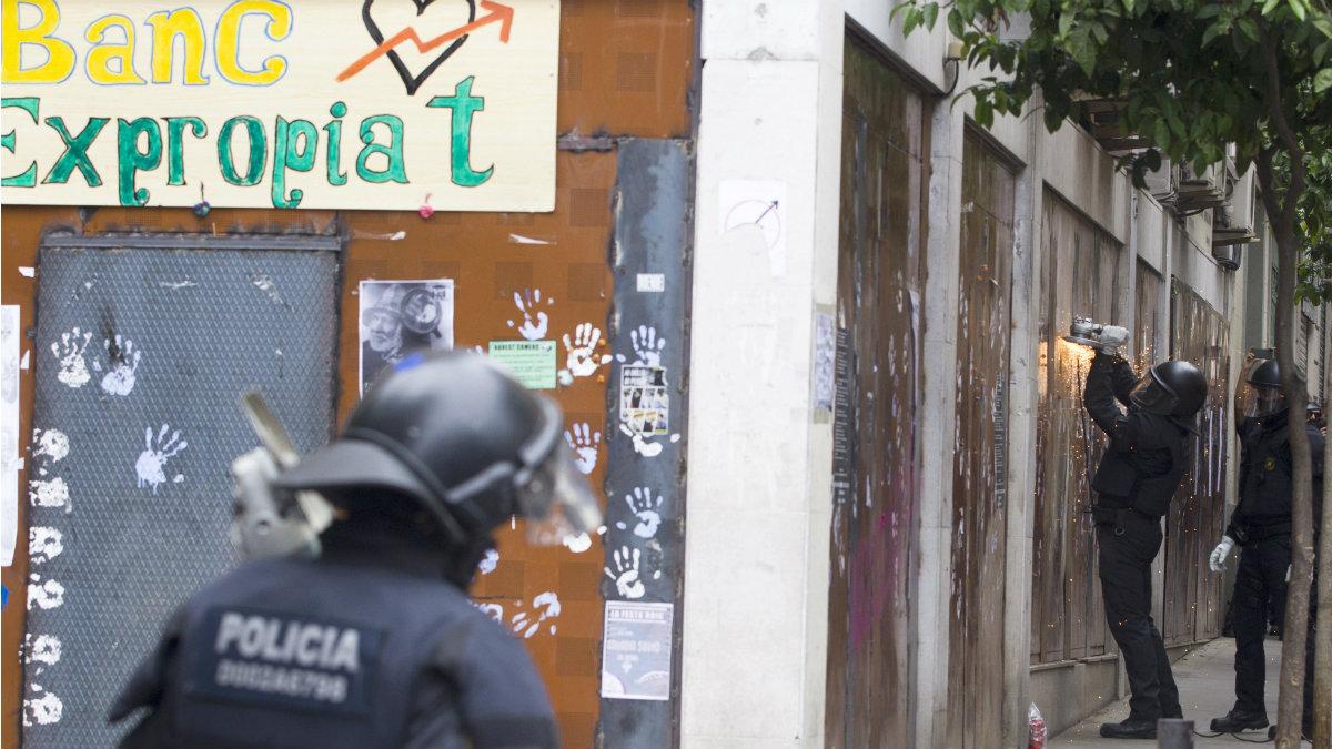 Los Mossos inician el butrón en la pared del 'banc expropiat' para desalojar a los okupas. (EFE)