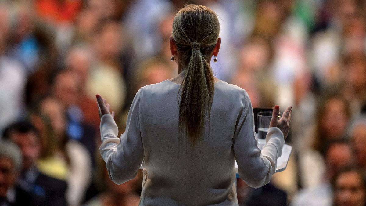 La presidenta Cifuentes en un mitin de espaldas. (Foto: AFP)