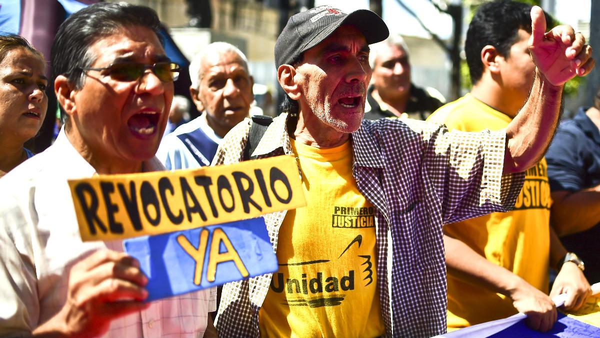 Un hombre exhibe una pancarta exigiendo el revocatorio contra Maduro (Foto: AFP).