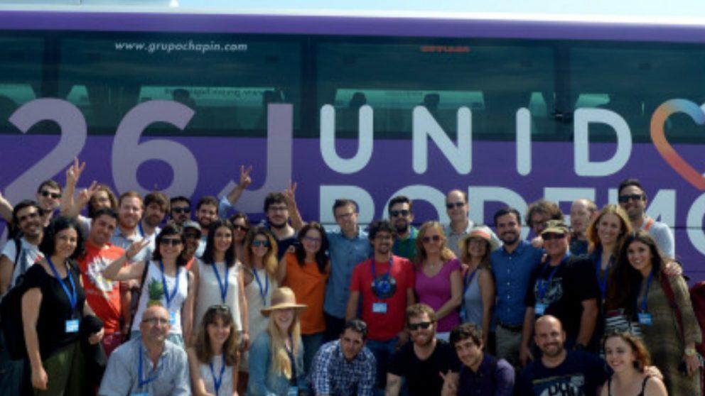 Militantes de Izquierda Unida y de Podemos posan junto al autobús de la coalición entre ambos partidos, Unidos Podemos.