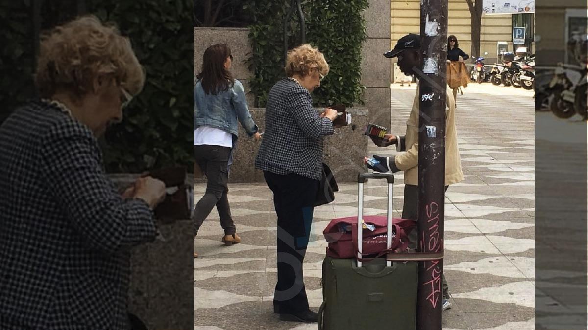 La exjueza Manuela Carmena comprando a un vendedor ilegal en Madrid. (Imagen exclusiva OKDIARIO)