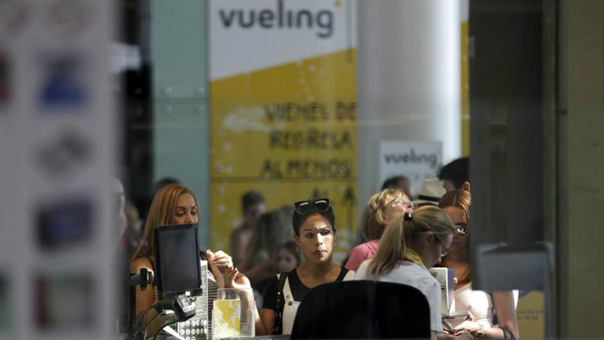 Personal de facturación de Vueling atiende a los viajeros en el Aeropuerto de El Prat. (Foto: EFE)