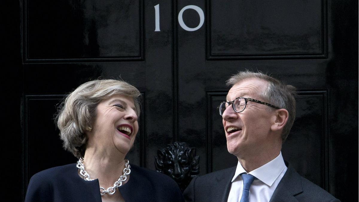 Theresa May y su marido Philip John May, a las puertas del 10 de Downing Street, desde donde llamó a Merkel y Hollande. (AFP)