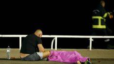 Un superviviente vela uno de los cuerpos tapado por una manta rosa, tras el atentado de Niza. (Reuters)