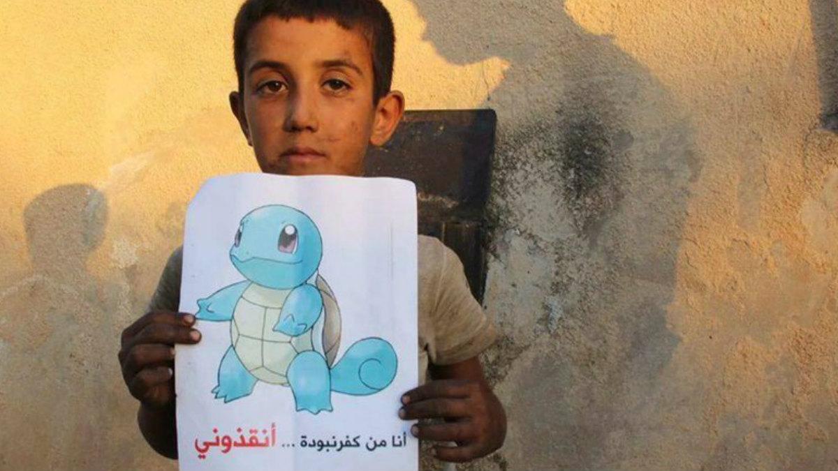 Un niño sirio sostiene un cartel con Squirtle, un ejemplar más de las criaturas que poblan el mundo de Pokémon Go, en el que se lee, en sirio, el mensaje Estoy en Siria, ven a salvarme.