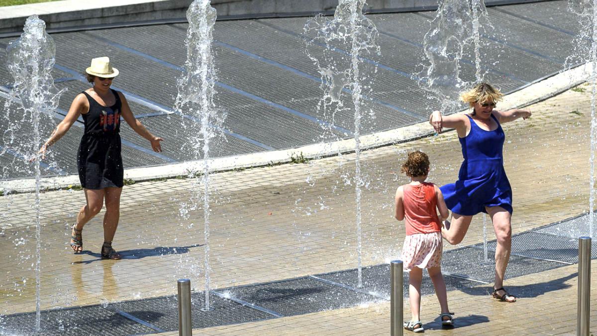 Varias personas se refrescan en una fuente pública. (Foto: EFE)