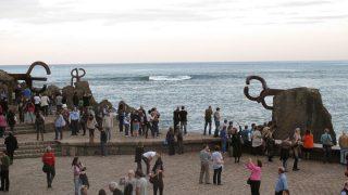 Transeúntes disfrutan del conjunto escultórico 'El Peinde del Vieno', de Chillida, en uno de los extremos de la bahía de La Concha. (Foto: CC)