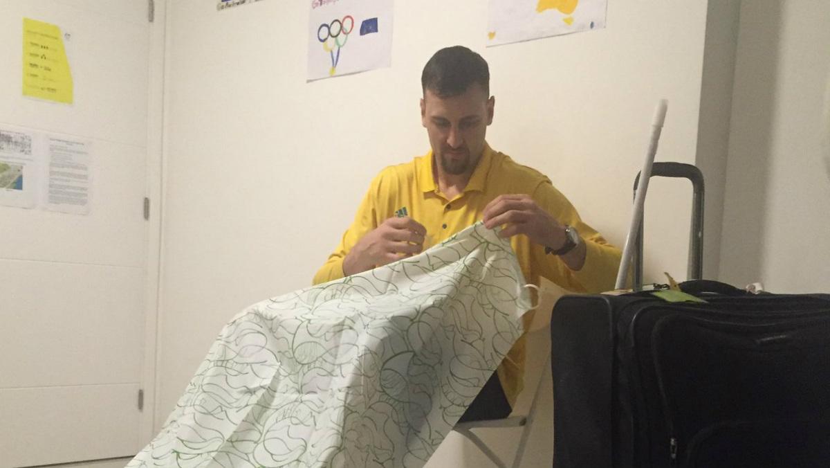 Bogut arreglando una cortina en la Villa Olímpica.