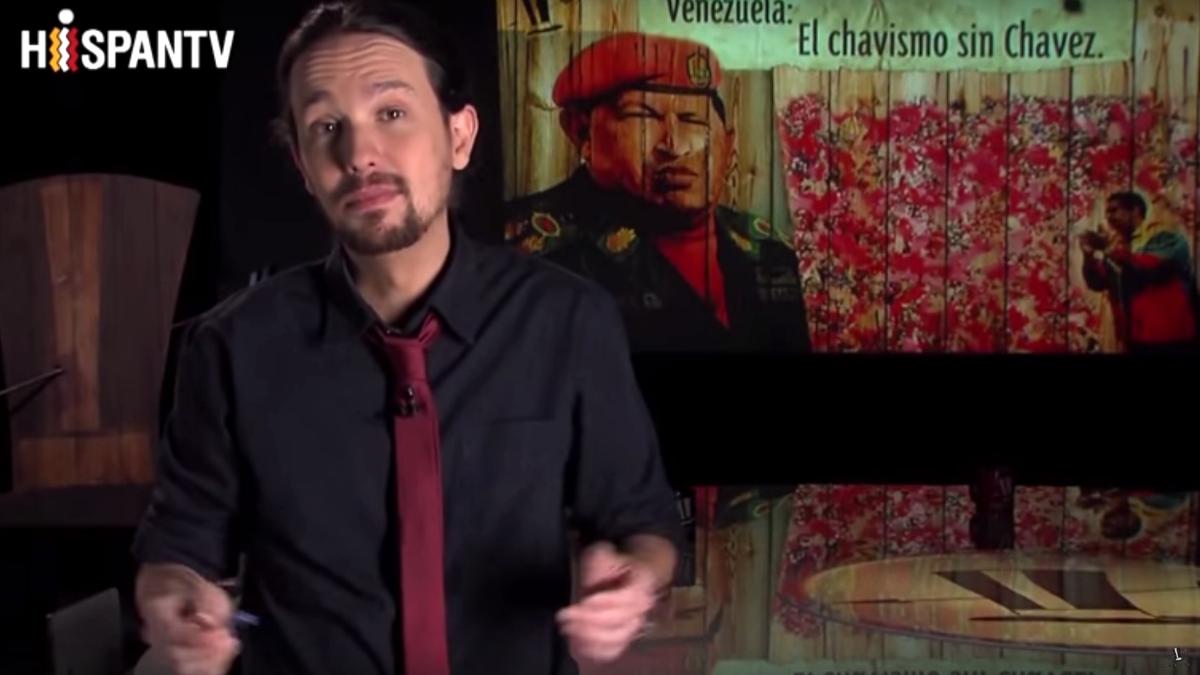 Pablo Iglesias con una imagen de Chávez al fondo.