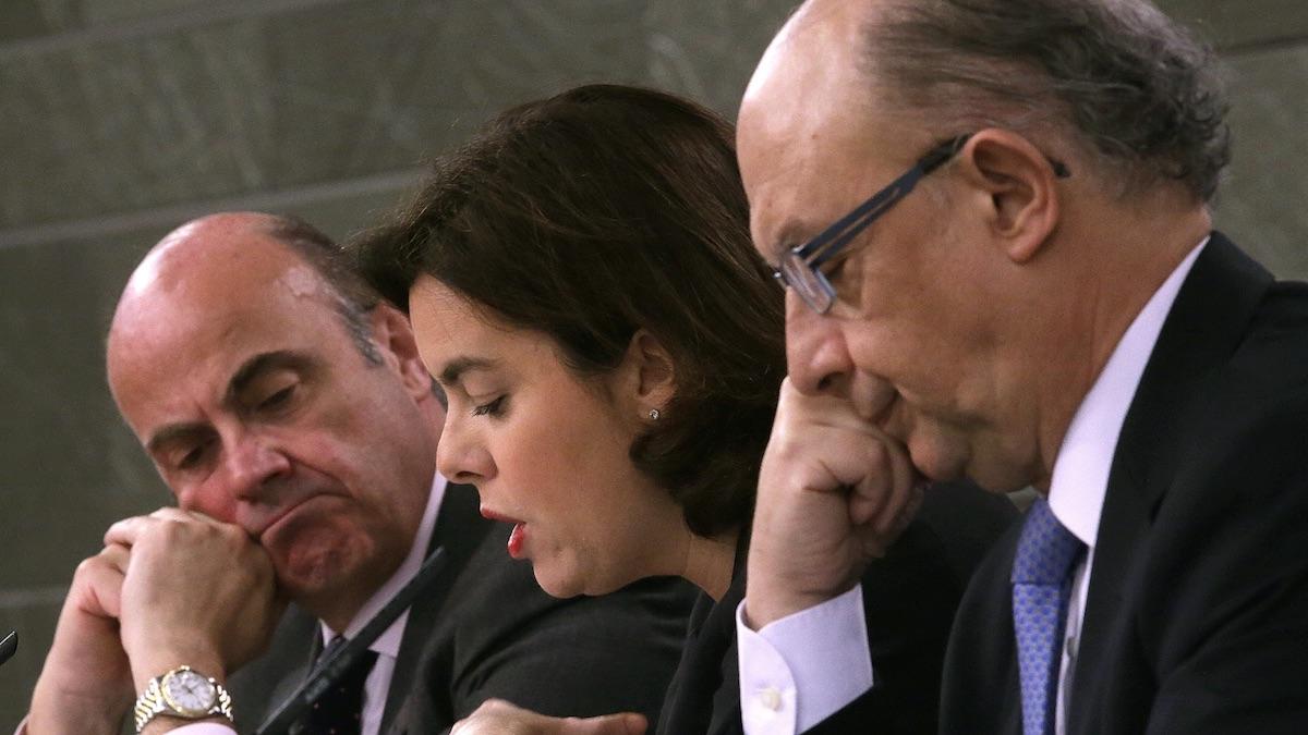 Luis de Guindos, junto a Soraya Sáenz de Santamaría y Cristóbal Montoro. (Foto: EFE)