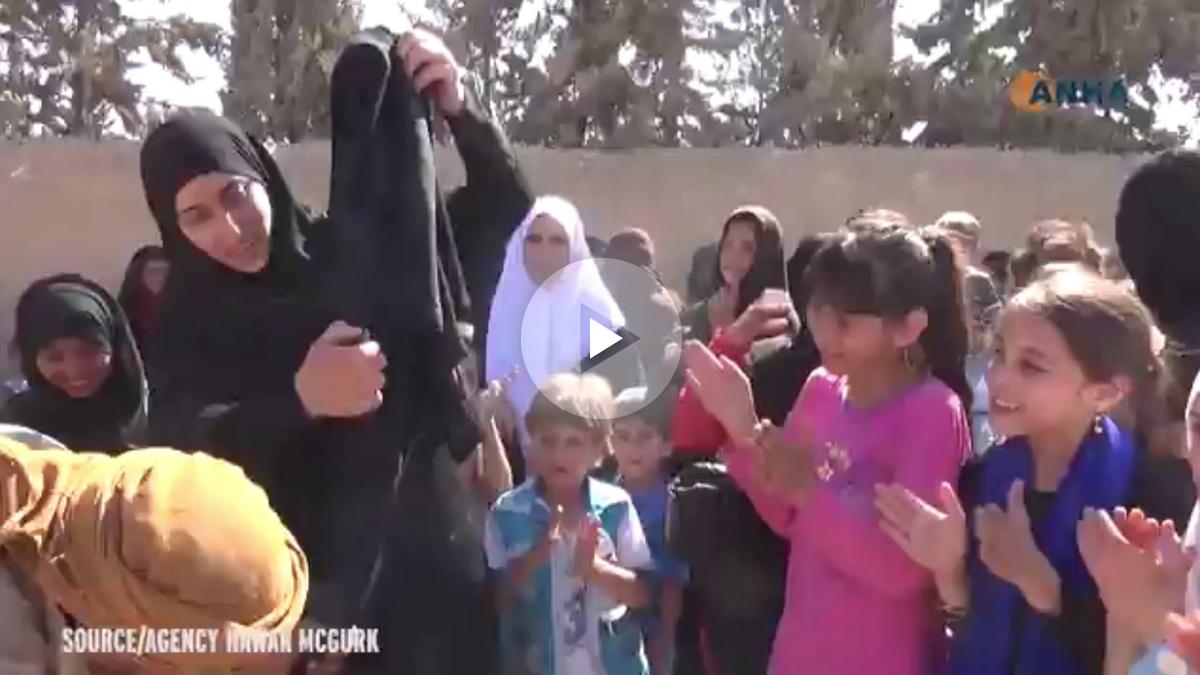 Mujeres queman sus burkas en Siria tras ser liberadas.