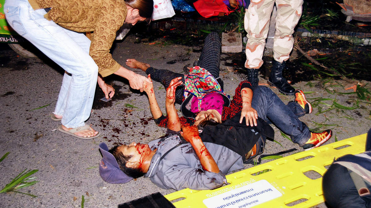 Un grupo de personas ayuda a dos heridos por una de las explosiones. (Foto: AFP)