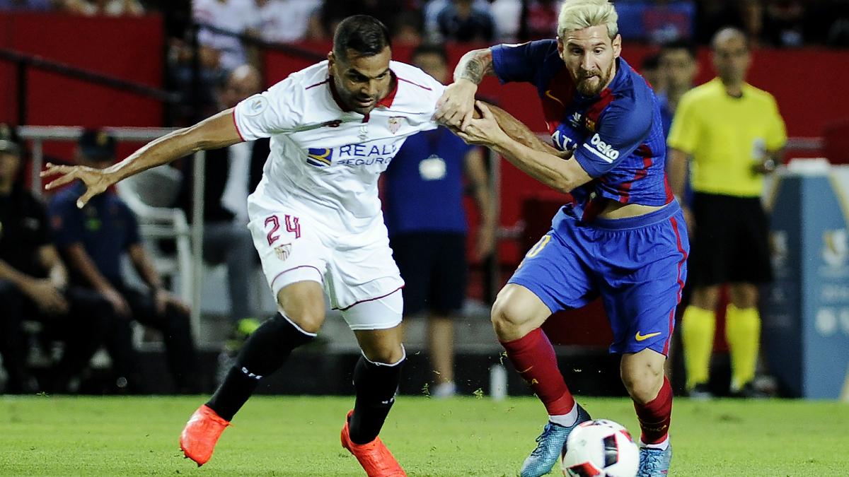 Messi y Mercado luchan por un balón