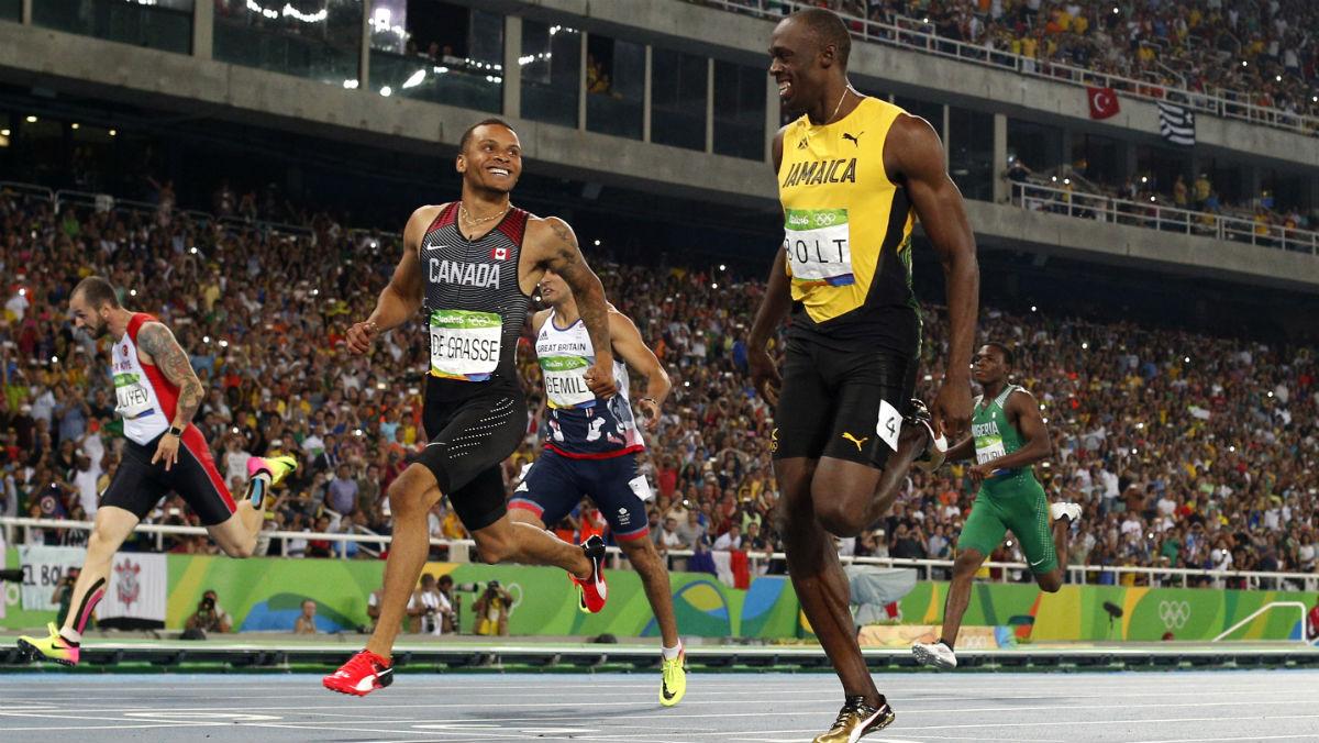 Bolt se ríe entrando en la meta con De Grasse. (AFP)
