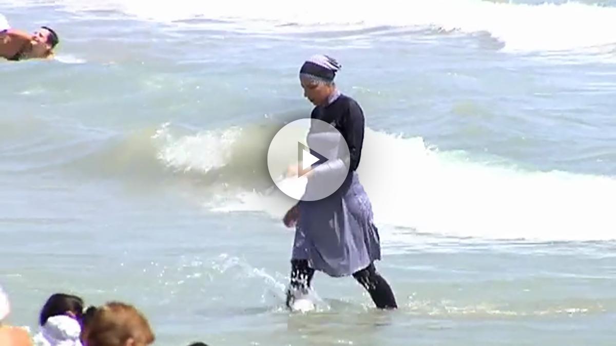 Una joven se baña con un burkini en una playa de Alicante.