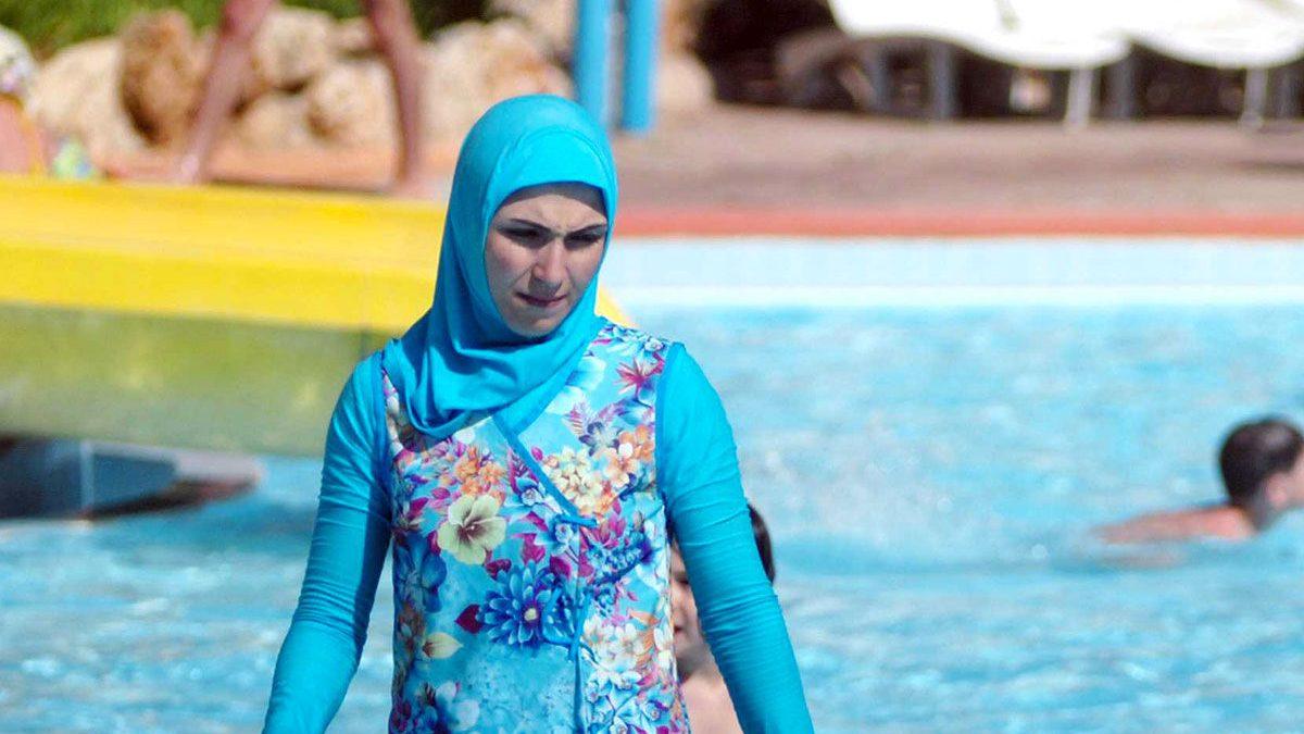 Una mujer se baña en una piscina llevando el polémico 'burkini' que ha sido prohibido en muchas playas de Francia.