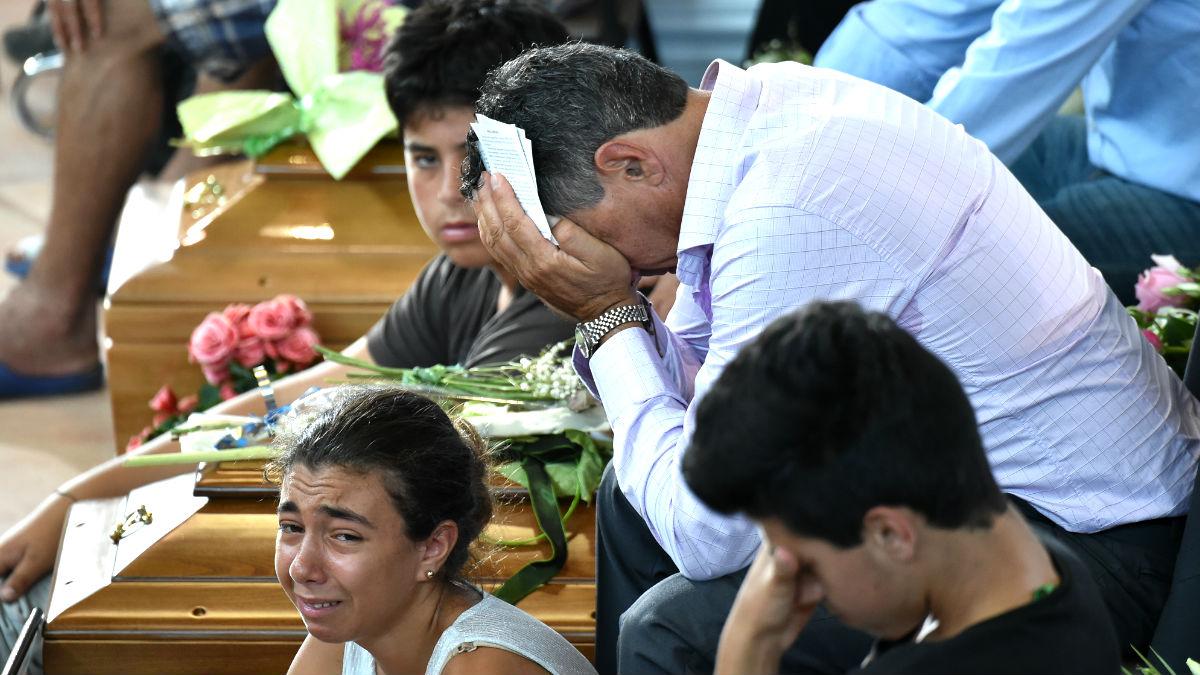 Varias personas lloran por las víctimas del terremoto durante el funeral (Foto: AFP).