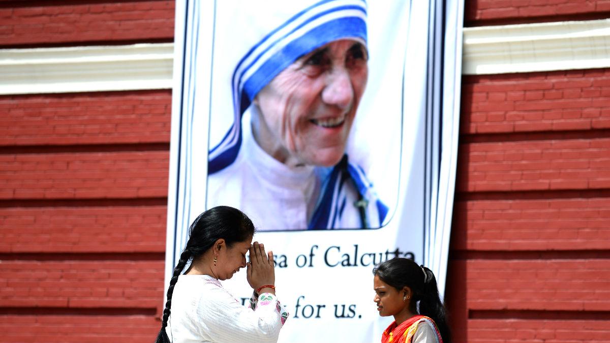 Dos mujeres rezan ante un cartel con la imagen de la Madre Teresa de Calcuta (Foto: AFP).