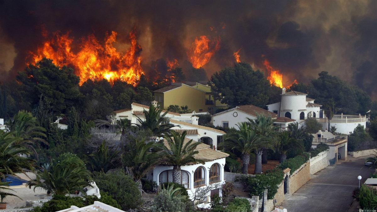 Las llamas alcanzan la urbanización Cumbres del Sol, junto a La Granadella, en Jávea (Alicante). (Foto: EFE)