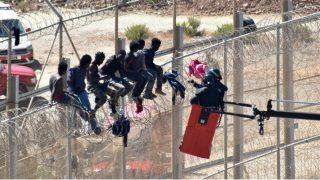 La Policía Nacional obliga a bajar a los inmigrantes de la verja de Ceuta. (EFE)