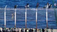 Inmigrantes encaramados a la verja fronteriza de Ceuta, con el mar al fondo.