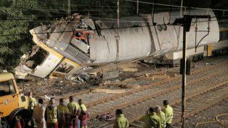 Los bomberos y operarios de Adif, elevan con grúas la locomotora del tren de la compañía Comboios de Portugal que cubría la línea entre Vigo y Oporto, que descarriló el viernes en la localidad pontevedresa de O Porriño causando cuatro muerto y casi medio centenar de heridos. (EFE)
