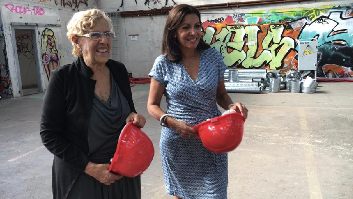 Las alcaldesas de Madrid y París vistando un futuro centro para refugiados. (Foto: TW)