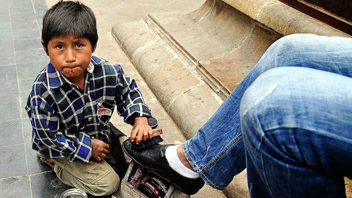 Un niño trabaja como limpiabotas en las calles de una ciudad de Bolivia. (Autor: César Catalán)