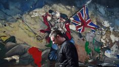 Un hombre camina delante de un grafitti que ilustra una portada de un disco del grupo británico Iron Maiden. (Foto: Getty)