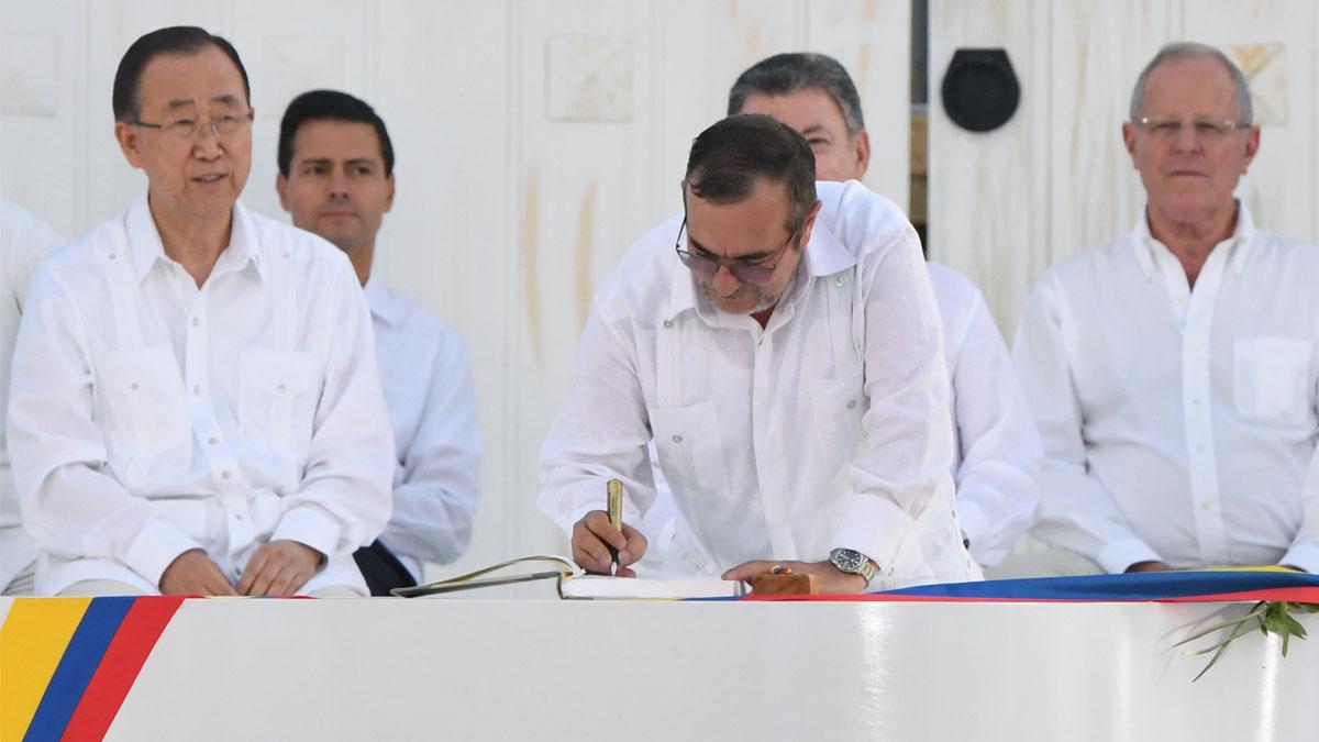 El líder de las FARC 'Timochenko', firma el documento ante la mirada del secretario general de la ONU' Ban Ki-moon. (Foto: AFP)