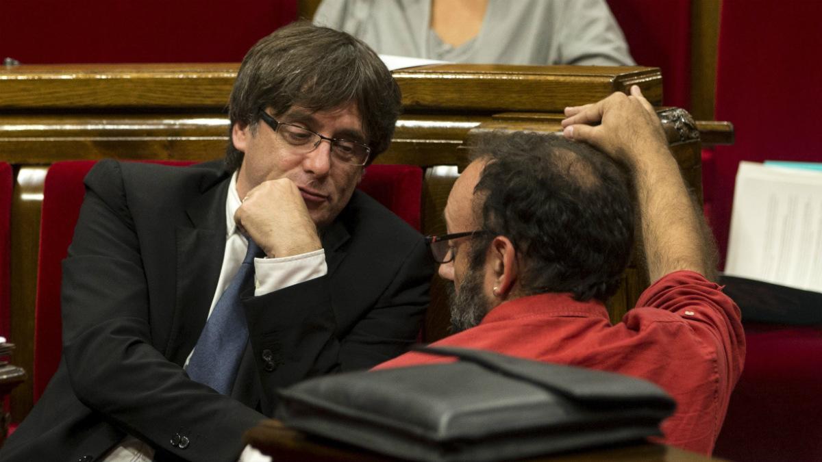 Carles Puigdemont departe con el diputado de la CUP Benet Salellas en el Parlamento de Cataluña. (EFE)