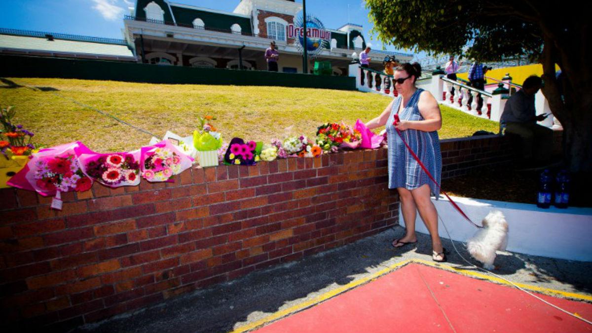 Familiares de las víctimas y afectados por el terrible accidente depositan flores en un muro del parque de atracciones Dreamworld, el más grande de Australia. AFP