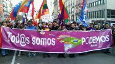 Sujetando el megáfono y la pancarta, en una manifestación multicultural de Podemos.