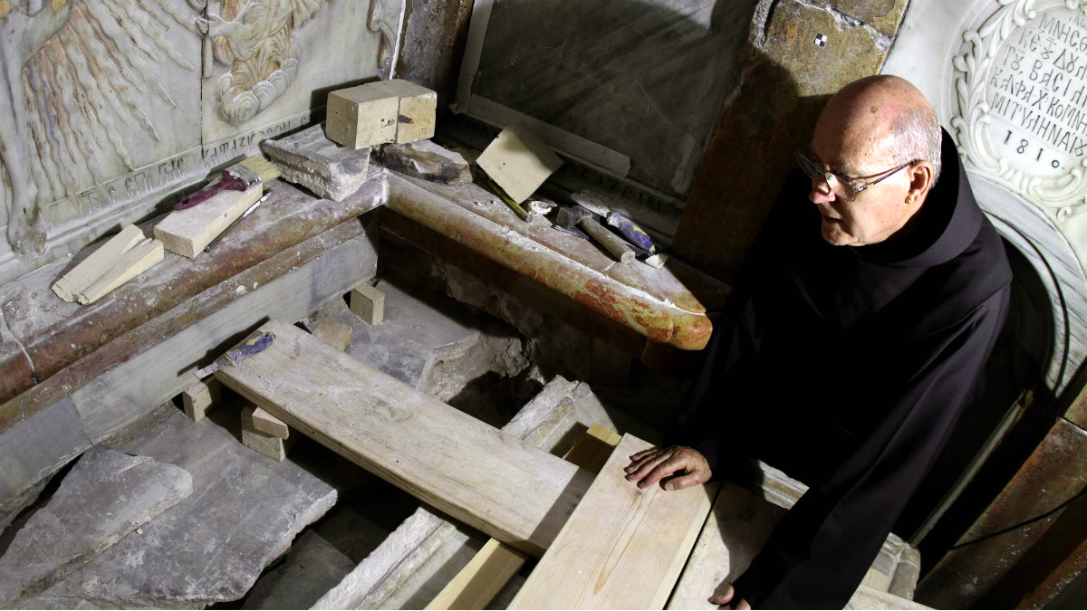 Un fraile franciscano, ante la tumba abierta de Jesucristo. (AFP)